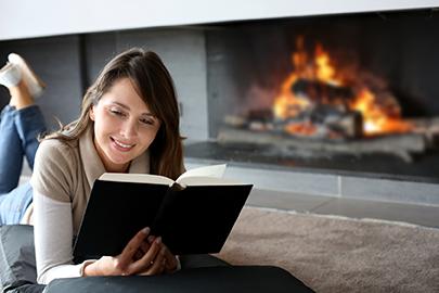 kobieta czyta książkę przy kominku
